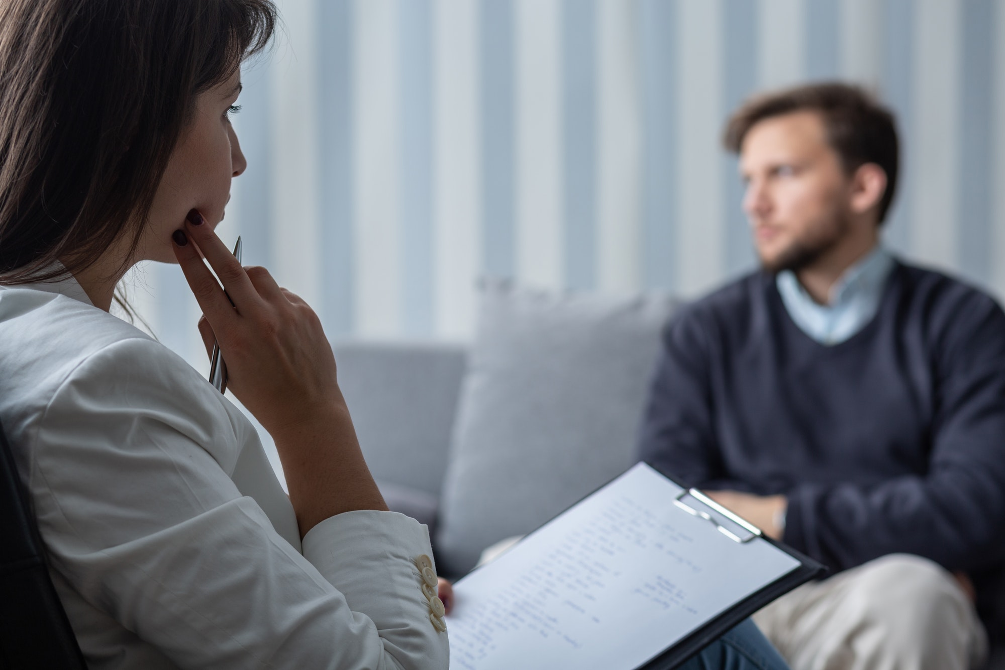 Thoughtful psychotherapist during session with sad patient with